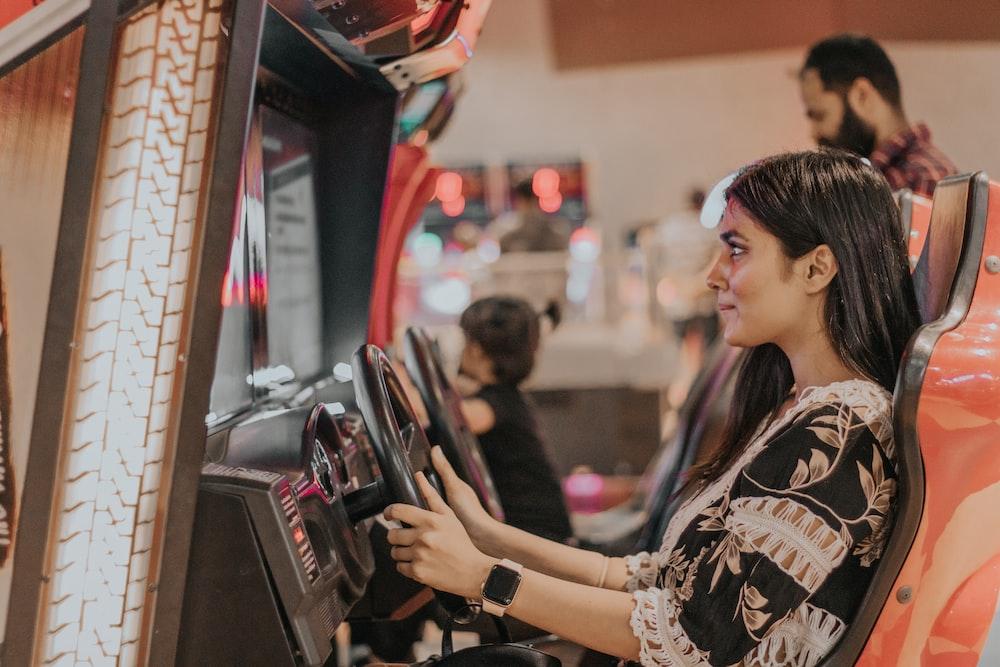 woman playing racing games at the arcade