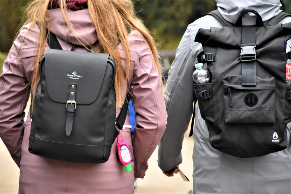 woman in black leather jacket carrying black leather backpack