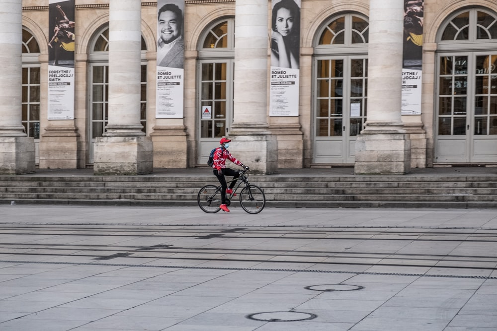 man in red jacket riding bicycle on sidewalk during daytime