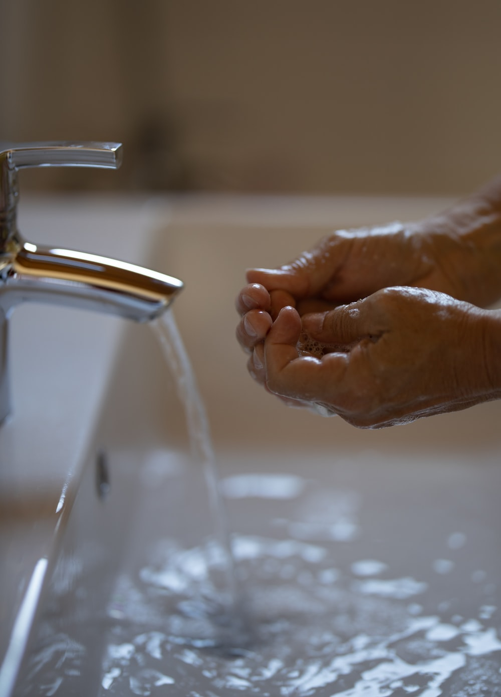 person washing hands on faucet