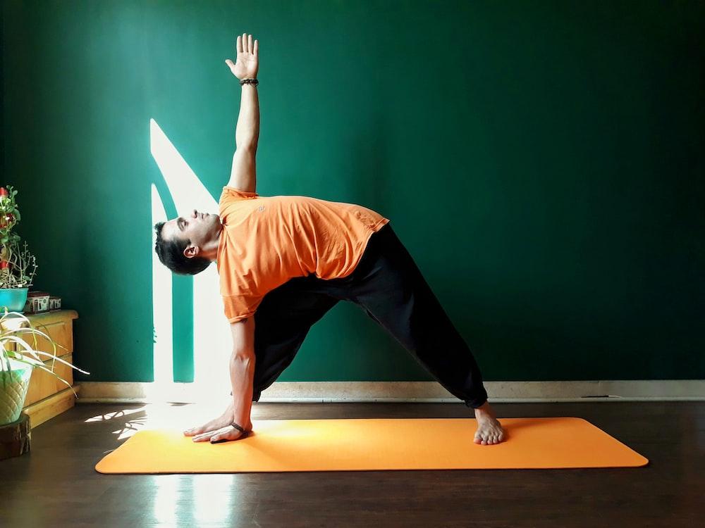 woman in orange tank top and black pants doing yoga