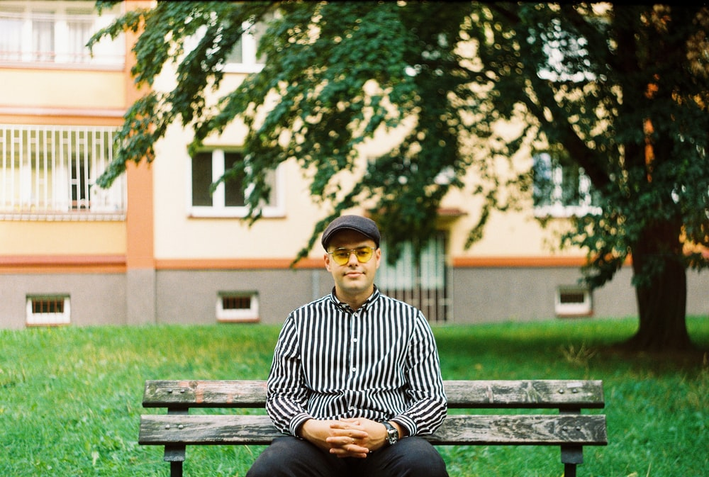 man in black and white striped long sleeve shirt sitting on bench