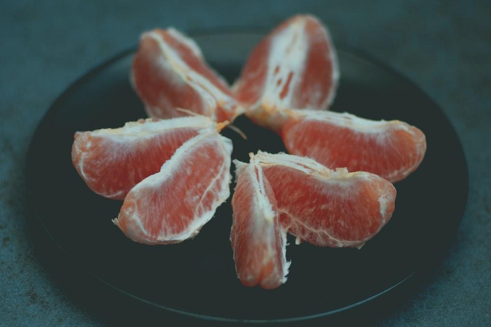 sliced red fruit on black plate