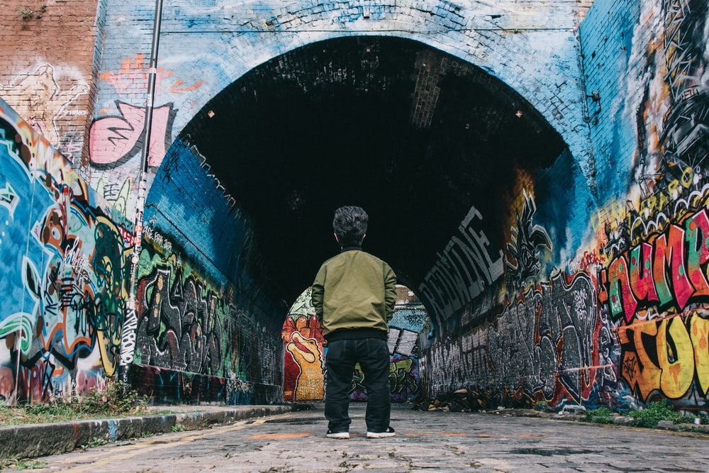 man in gray jacket and blue denim jeans standing beside graffiti wall during daytime
