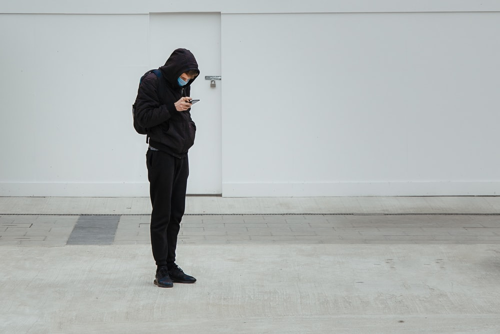 man in black hoodie and black pants standing near white wall