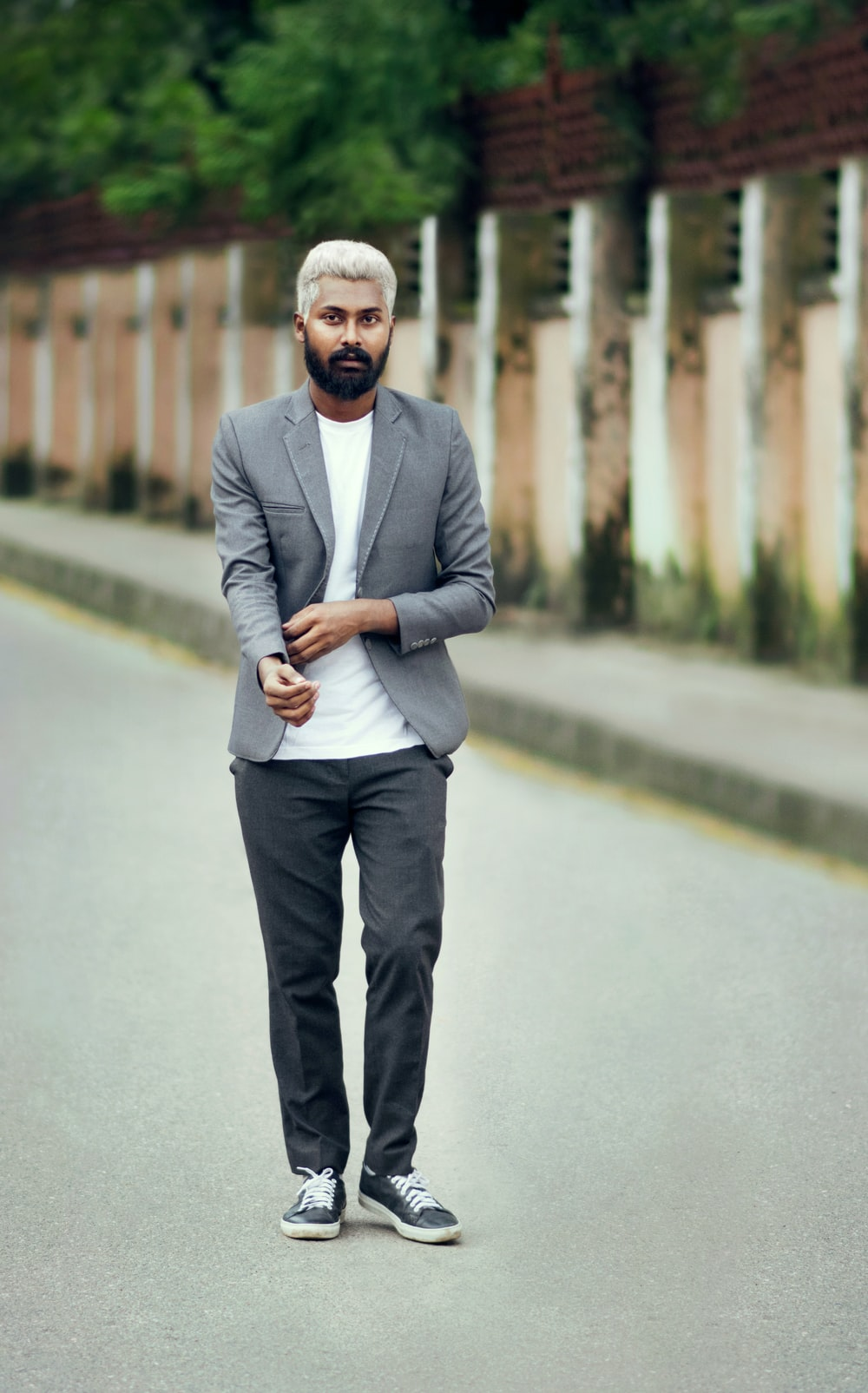man in gray suit standing on gray concrete road during daytime