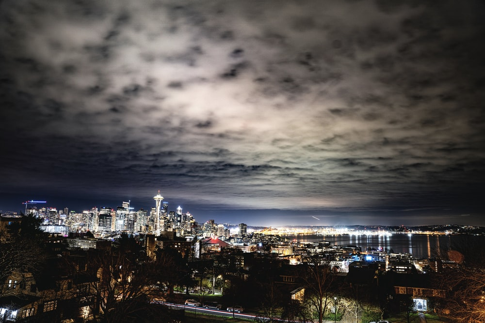 city skyline under gray cloudy sky during night time