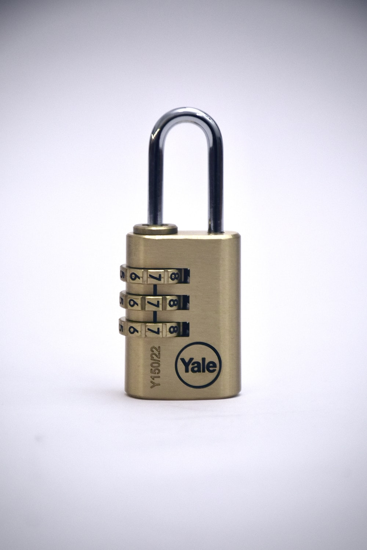 gold padlock on white surface
