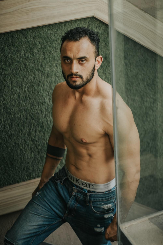 topless man in blue denim jeans