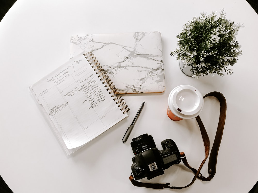 black nikon dslr camera on white notebook beside white ceramic mug