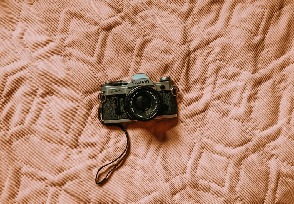 black and silver dslr camera on white textile