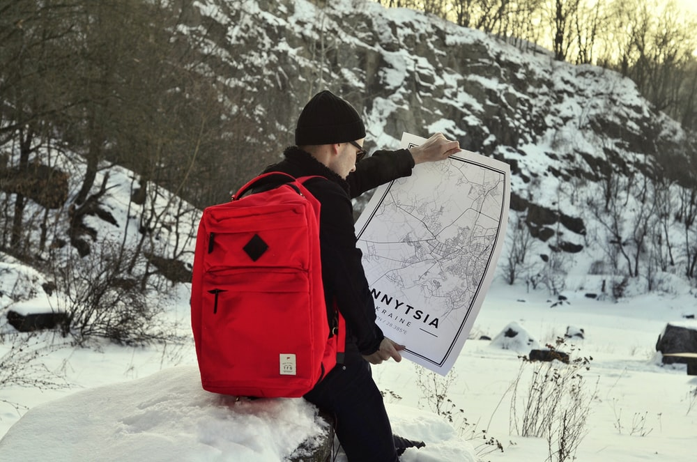 man in black jacket carrying red and black backpack standing on snow covered ground during daytime