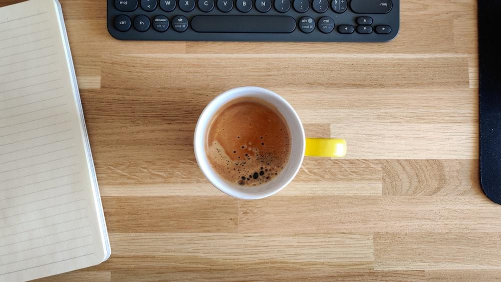 yellow ceramic mug on brown wooden table