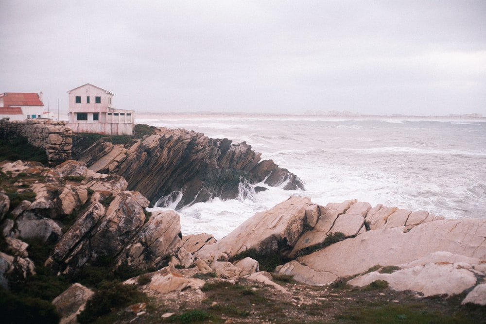 white and brown house on brown rocky shore near ocean water during daytime