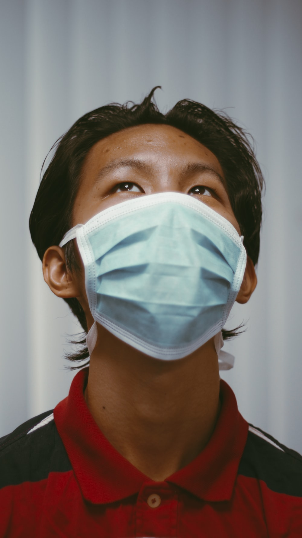 woman in red shirt wearing white face mask