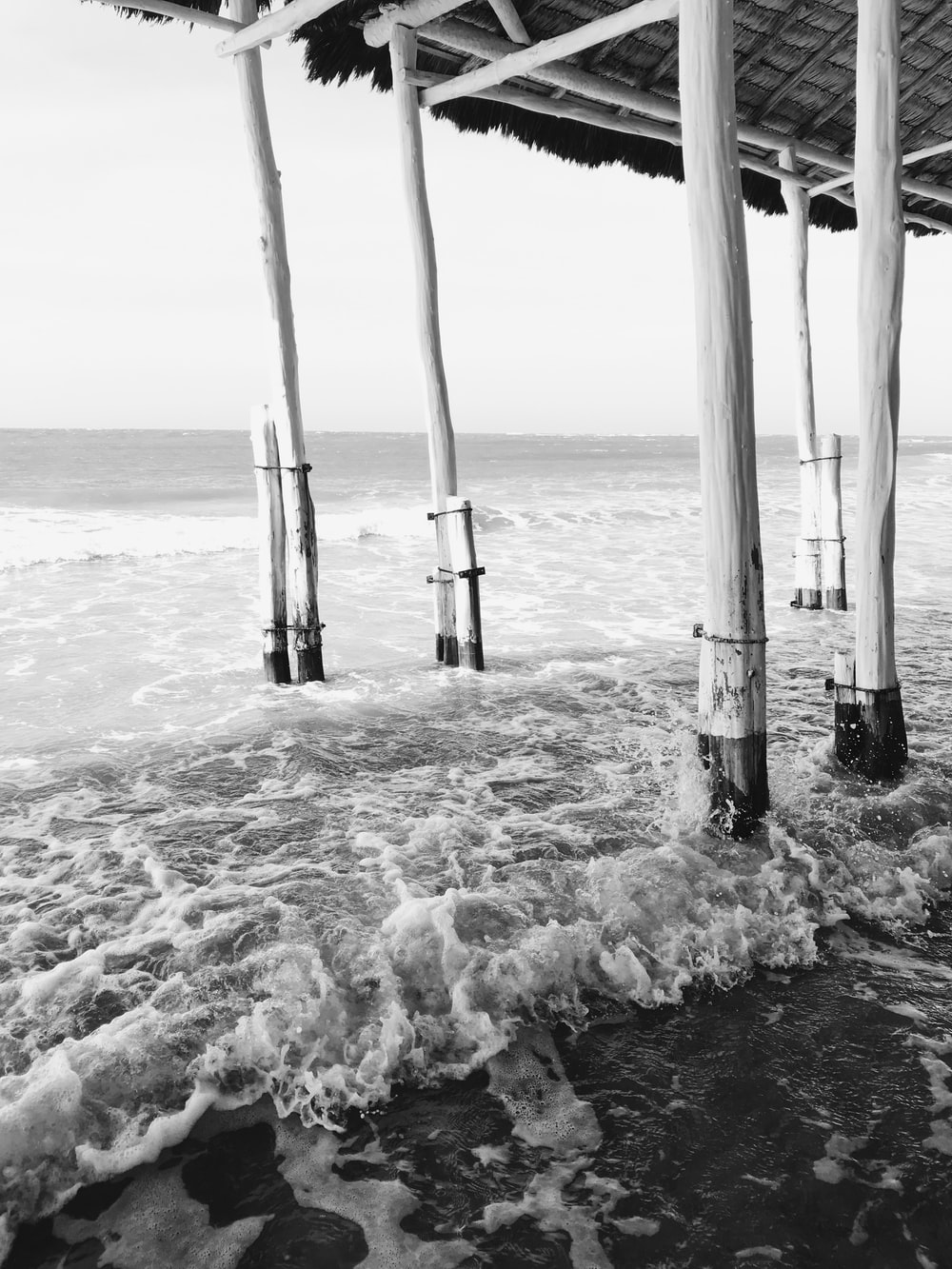 grayscale photo of sea waves crashing on shore
