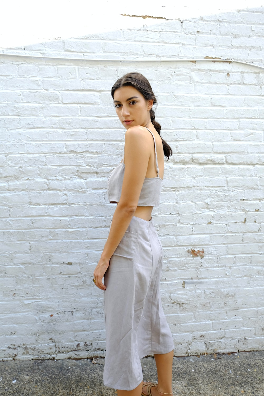 woman in white tank top and white pants standing beside brick wall