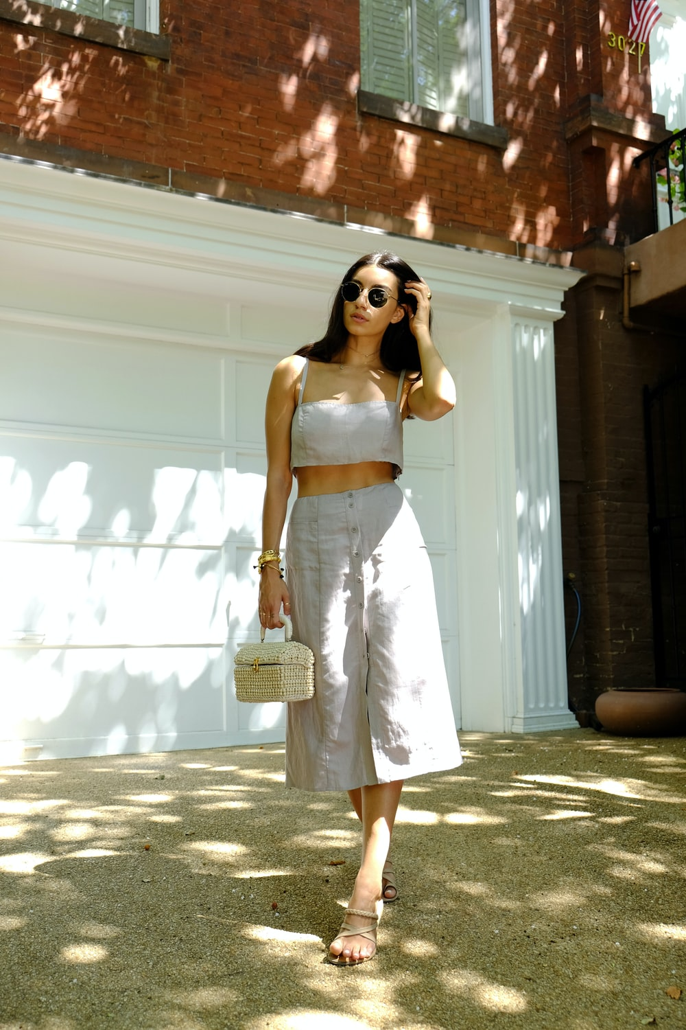 woman in white spaghetti strap dress wearing sunglasses standing near white wall during daytime