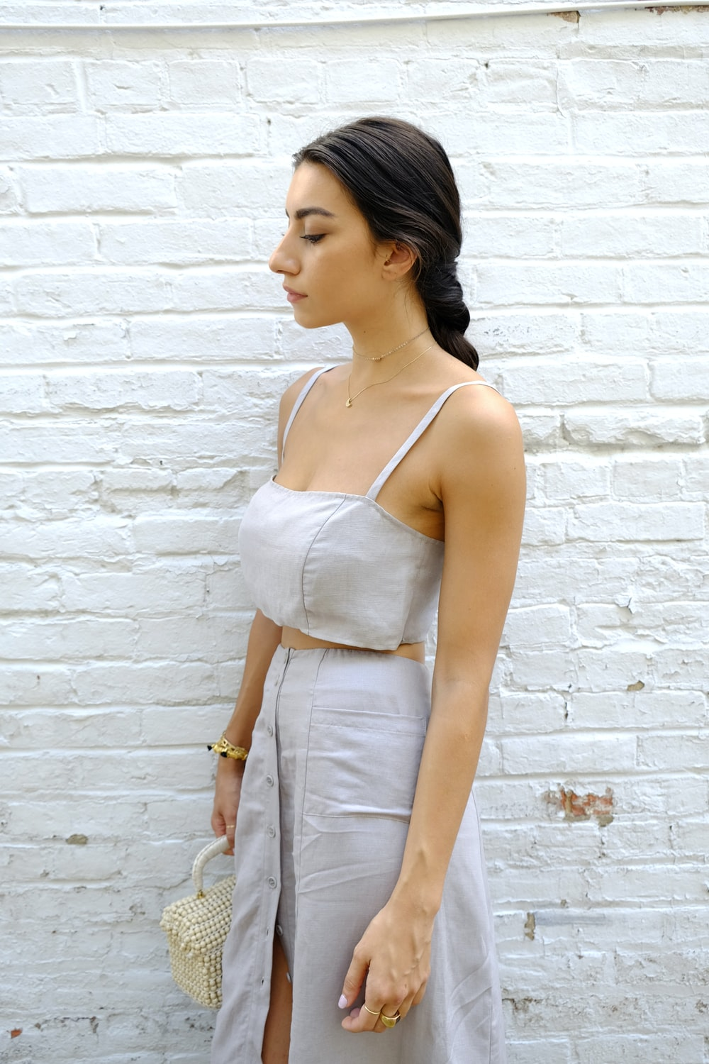 woman in white spaghetti strap top and gray pants leaning on white brick wall