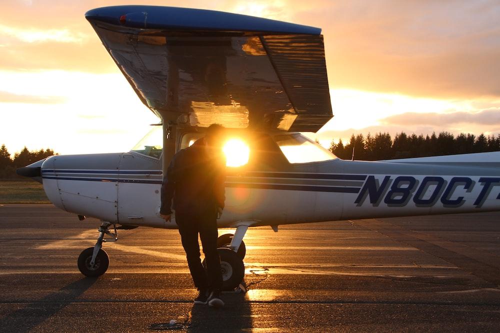 man in black jacket and black pants standing beside airplane