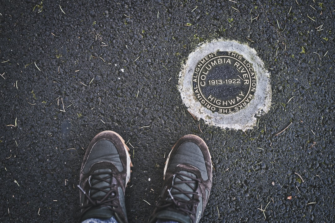 Old Columbia River Highway marker on the new State Trail.   Brass marker in asphalt with shoes.