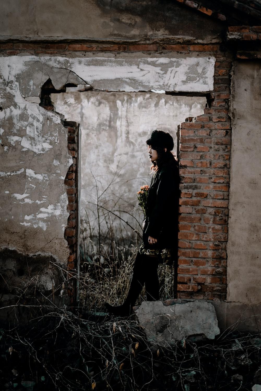 man in black coat standing beside brown brick wall during daytime