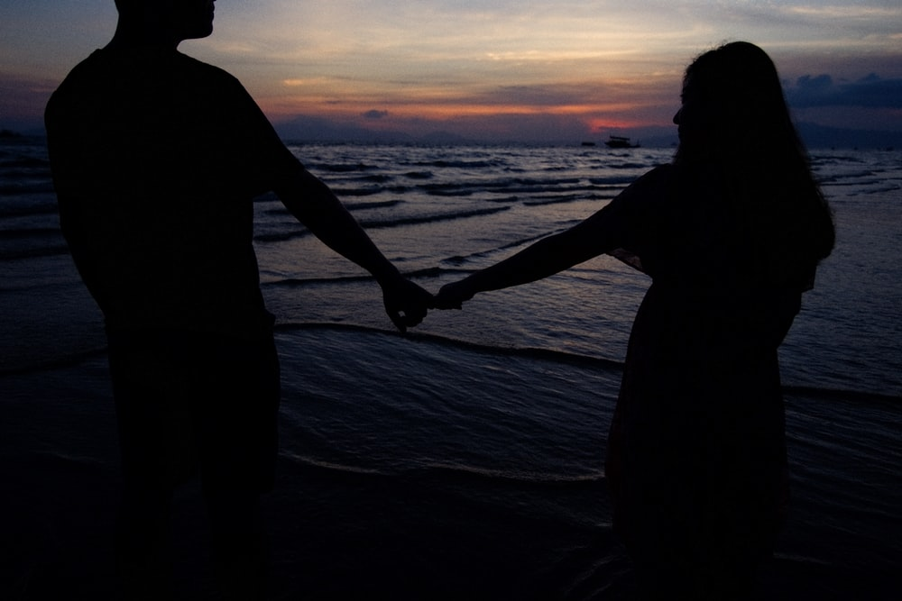 silhouette of man and woman holding hands while walking on beach during sunset