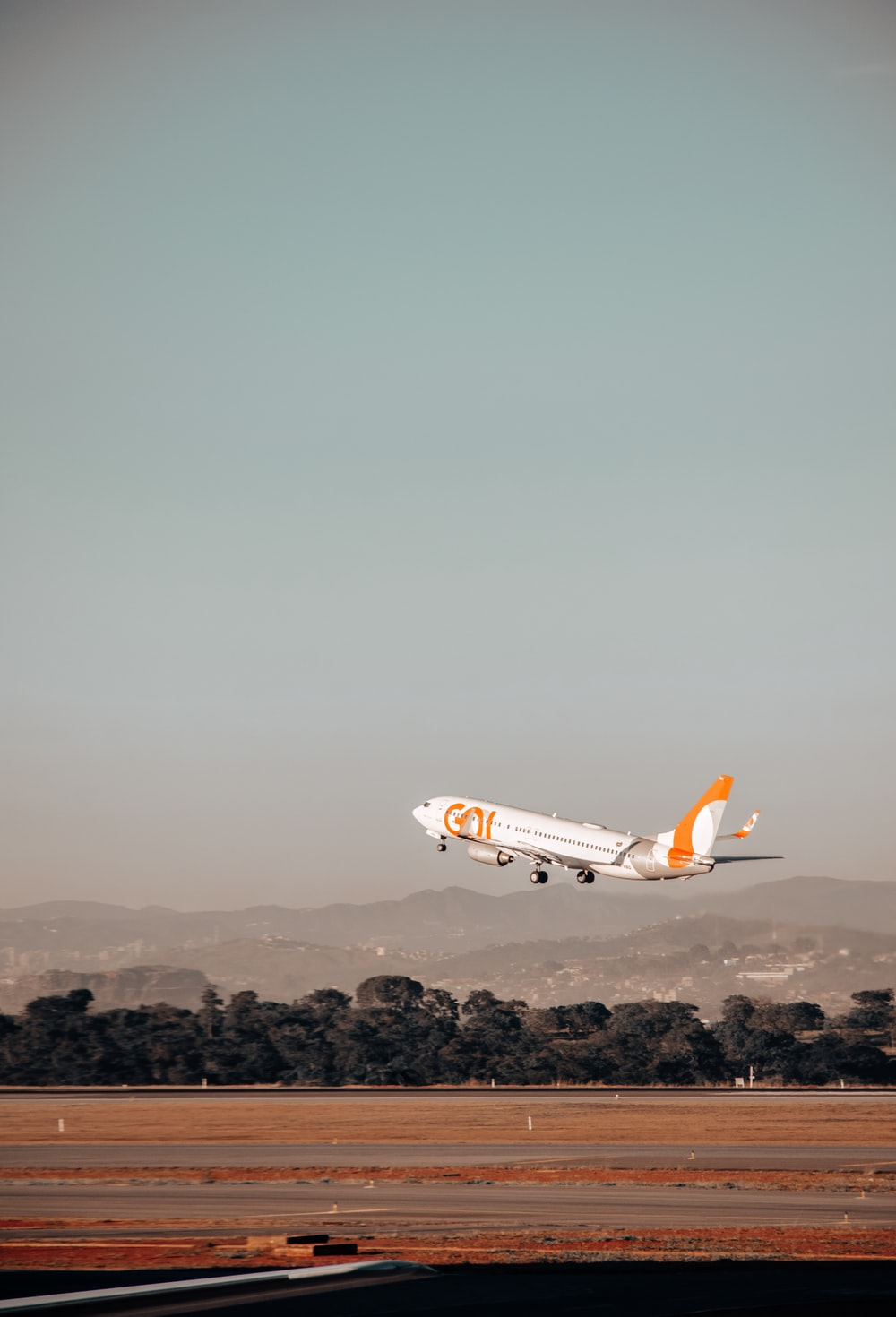 white and orange airplane in mid air during daytime