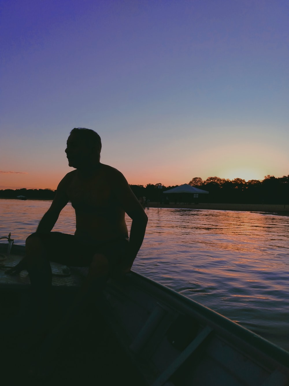 silhouette of man sitting on boat during sunset