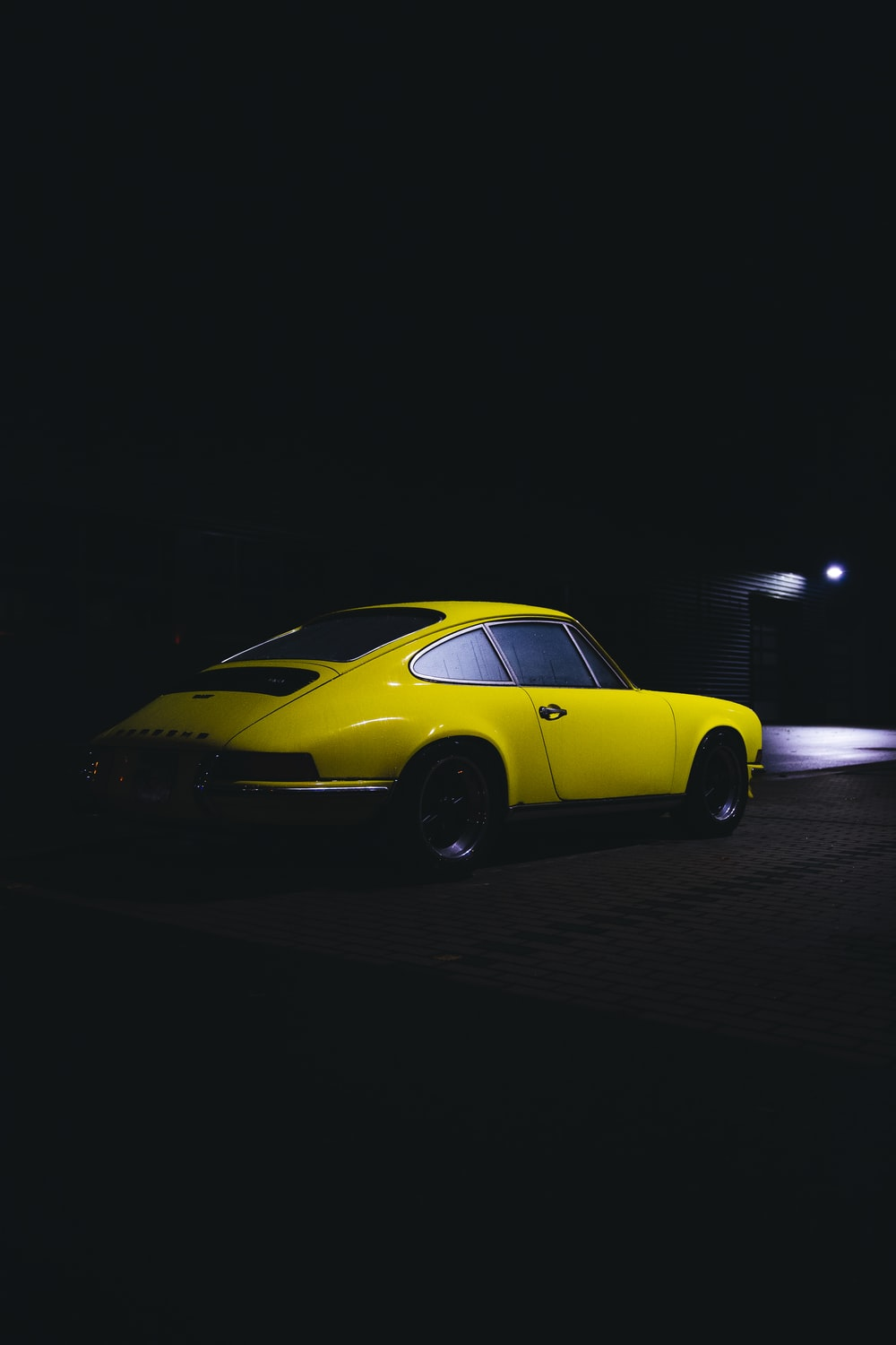 yellow coupe on black asphalt road during night time