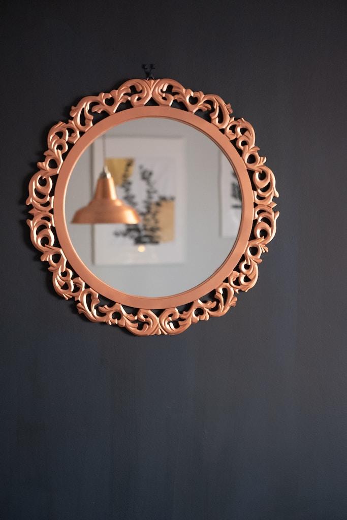 brass round framed mirror on black textile