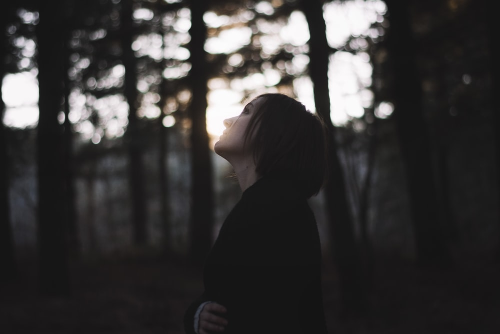 woman in black coat standing in front of trees during daytime