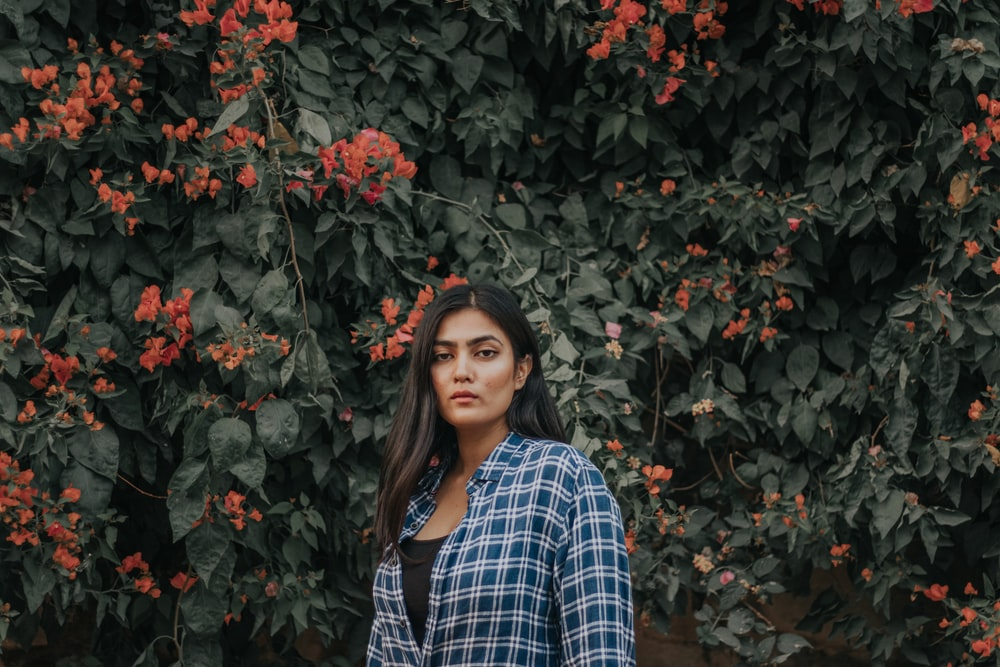 woman in blue and white plaid dress shirt standing beside red flowers