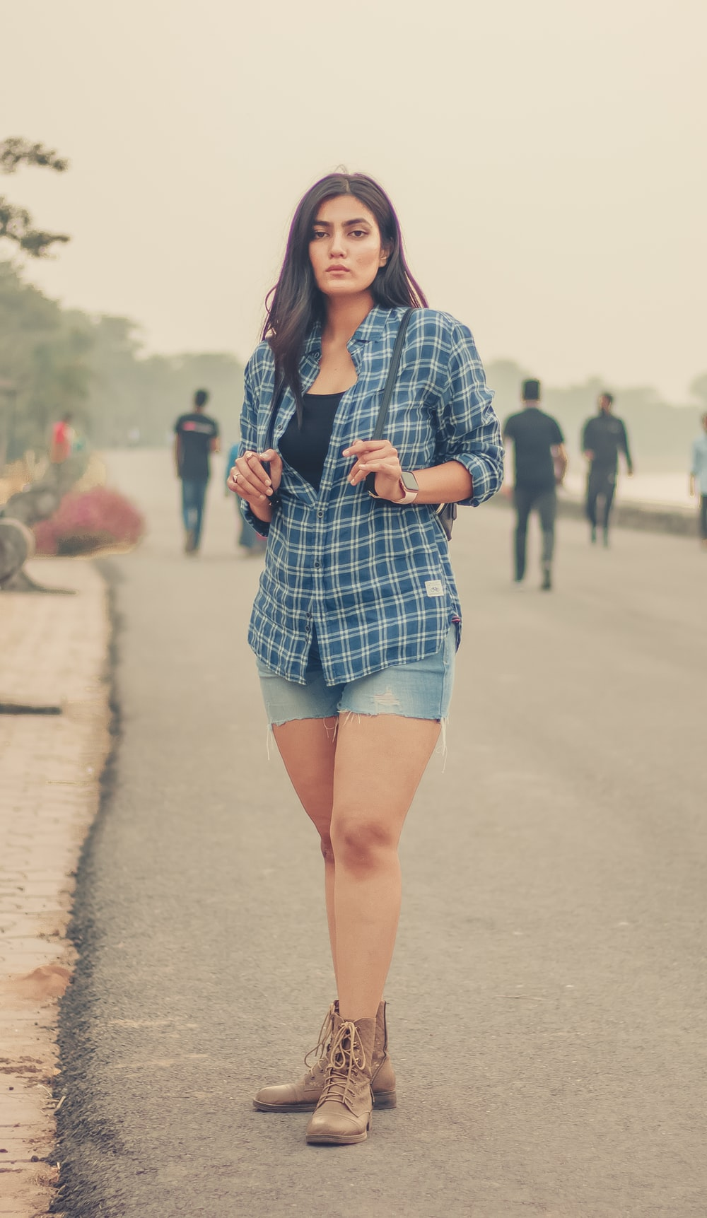 woman in blue and white plaid button up long sleeve shirt and blue denim shorts standing