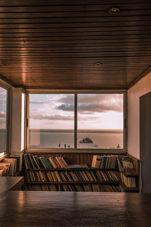 brown wooden book shelf near window