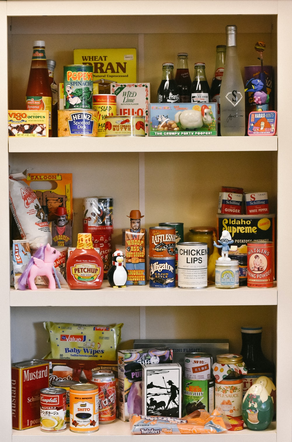 assorted cans on white wooden shelf