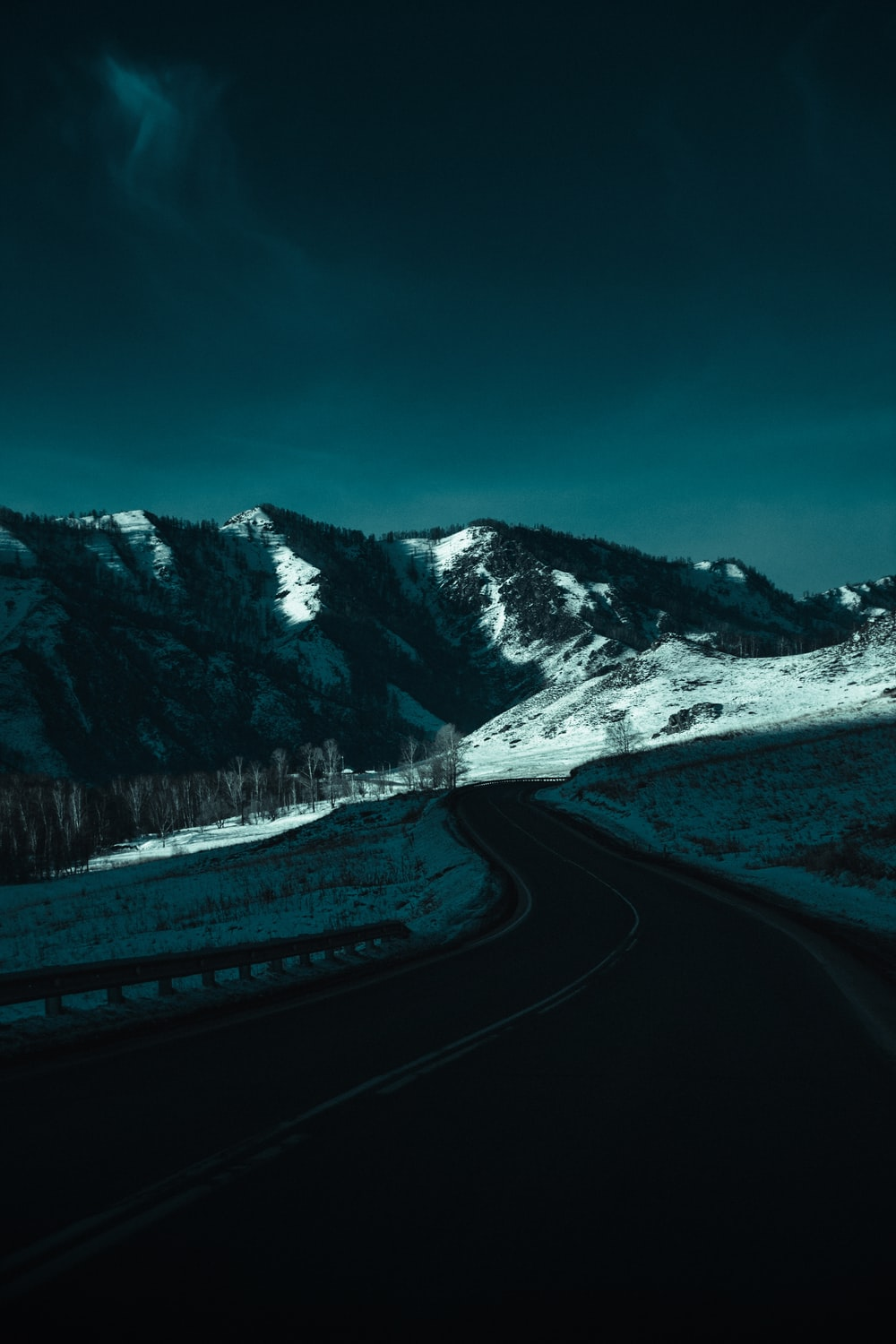 gray road near snow covered mountain during daytime
