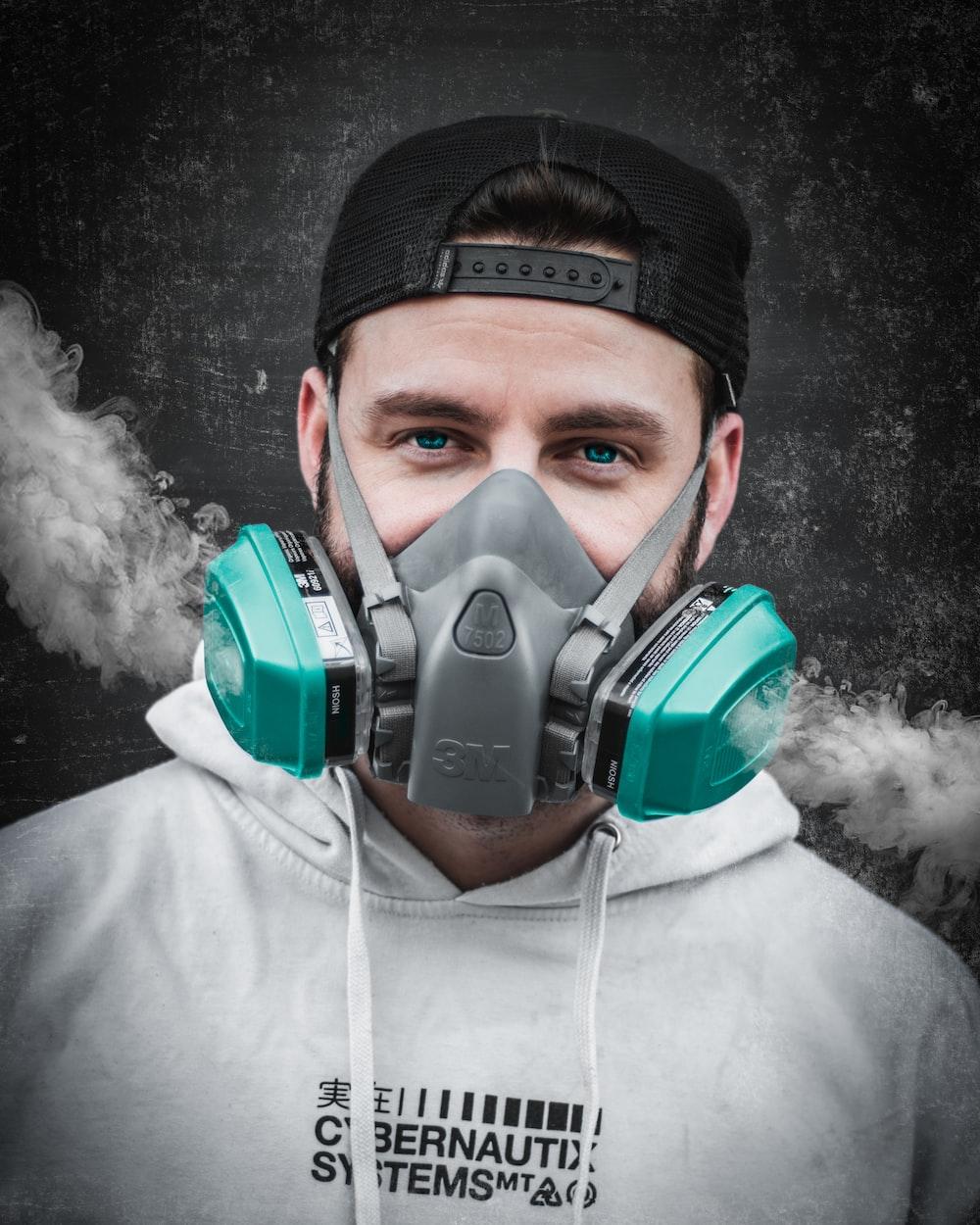 man in white hoodie wearing green gas mask