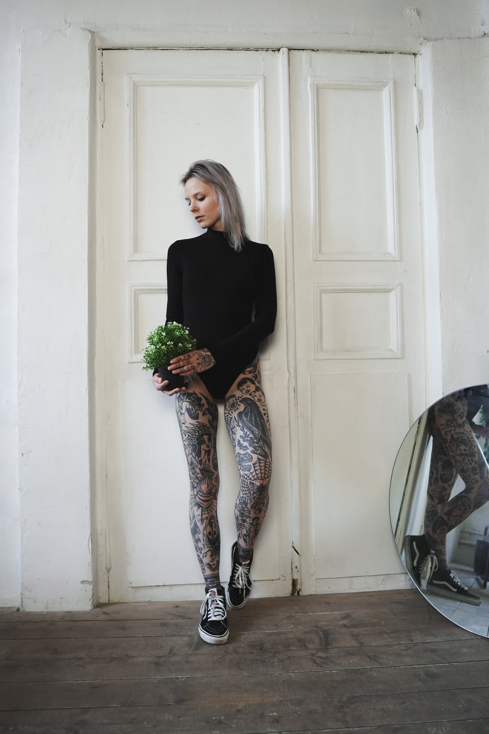 woman in black long sleeve shirt and gray pants holding bouquet of flowers