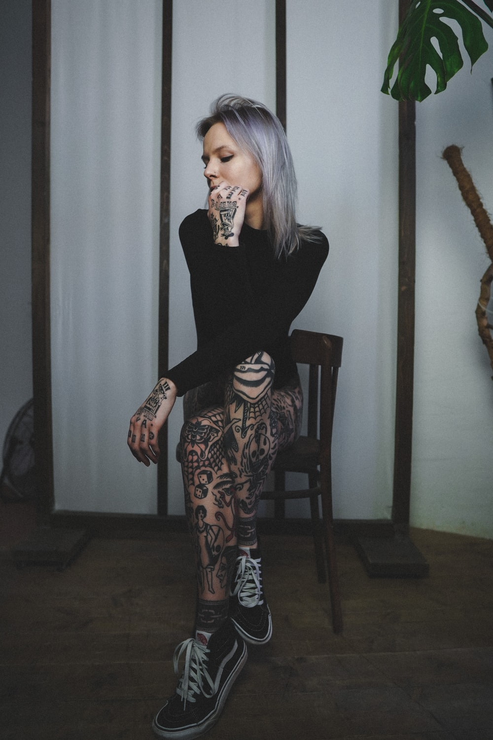 woman in black long sleeve shirt and black and white pants standing near brown wooden chair