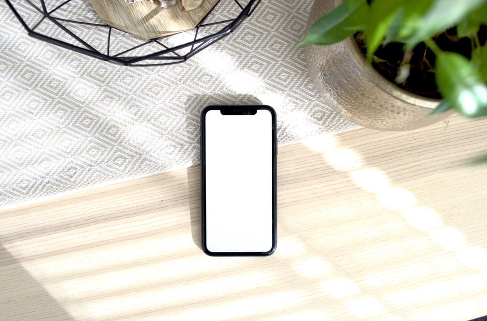 white iphone 5 c on brown wooden table