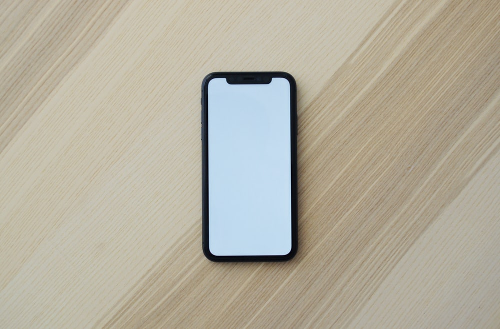 white smartphone on brown wooden table