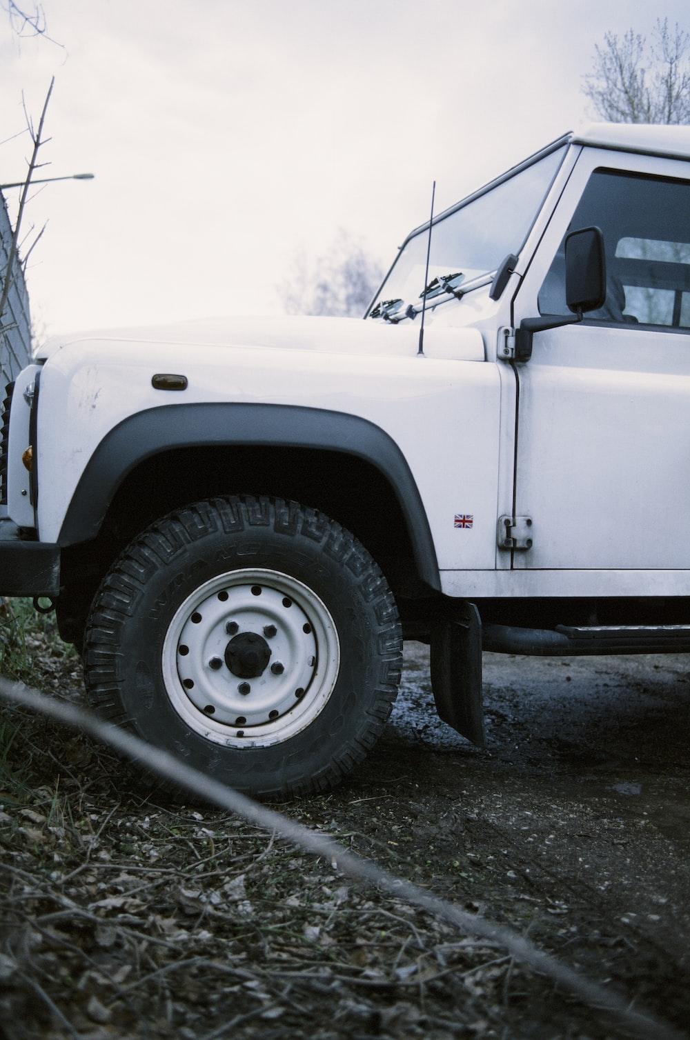 white jeep wrangler on dirt road during daytime