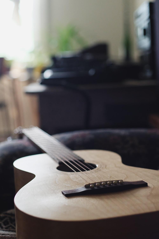 brown acoustic guitar on black chair
