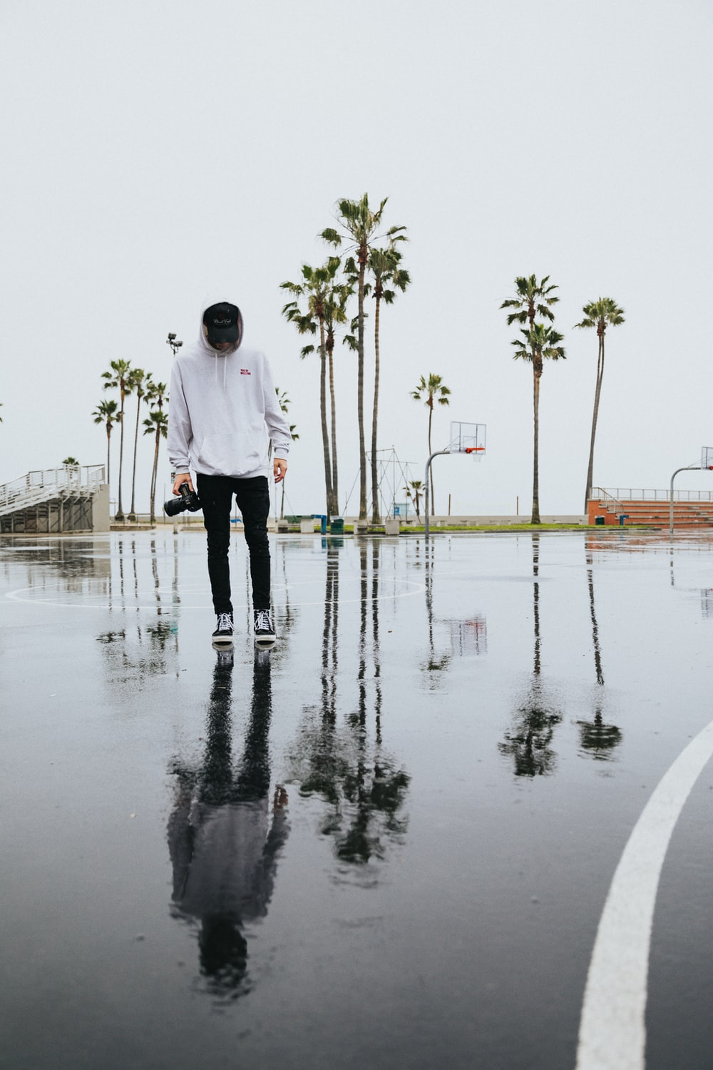 man in white dress shirt and black pants standing on wet ground during daytime