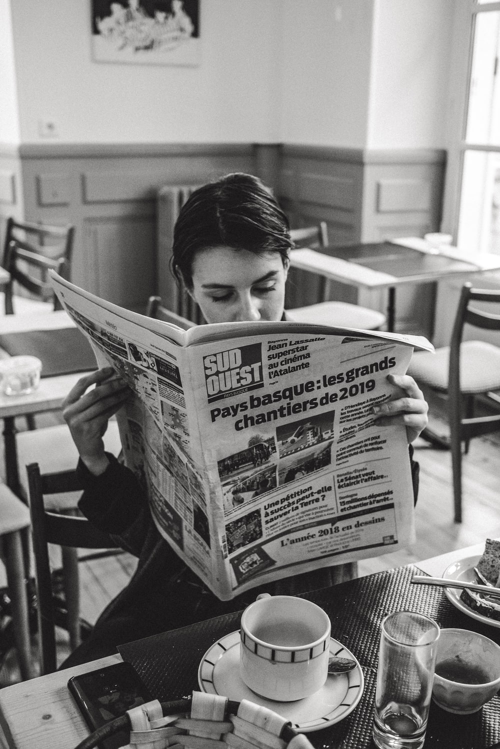 grayscale photo of man reading newspaper