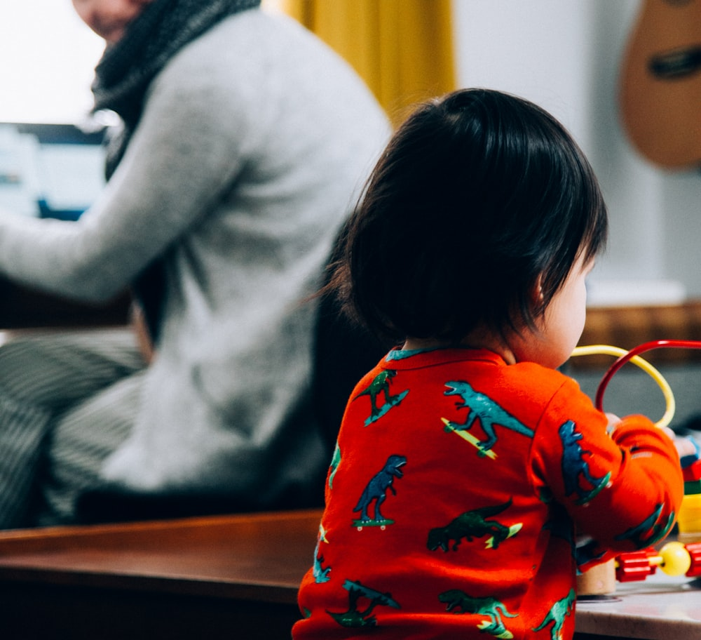 child in red and white floral long sleeve shirt sitting on brown wooden table