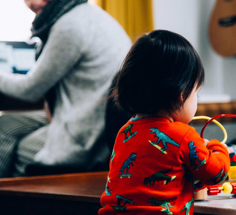 Criança brincando com adulto em home office ao fundo