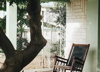 brown wooden rocking chair under green tree