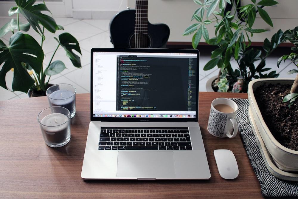macbook pro beside white ceramic mug on brown wooden table